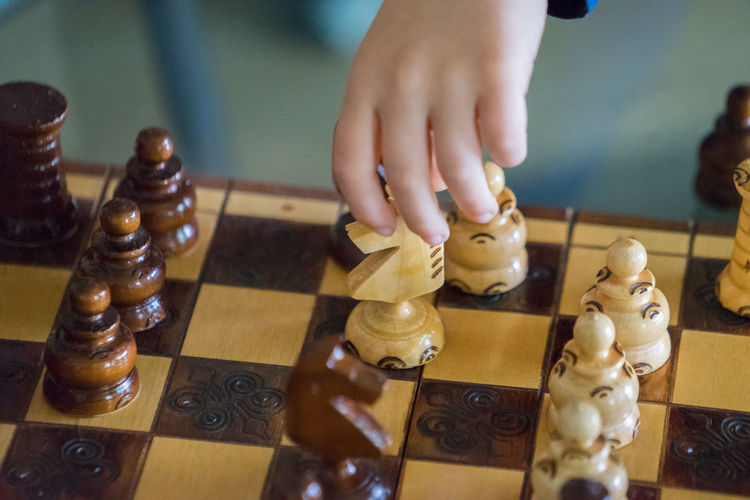 Close-up of baby playing chess at home