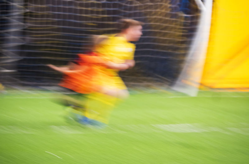 Blurred motion of man running on soccer field