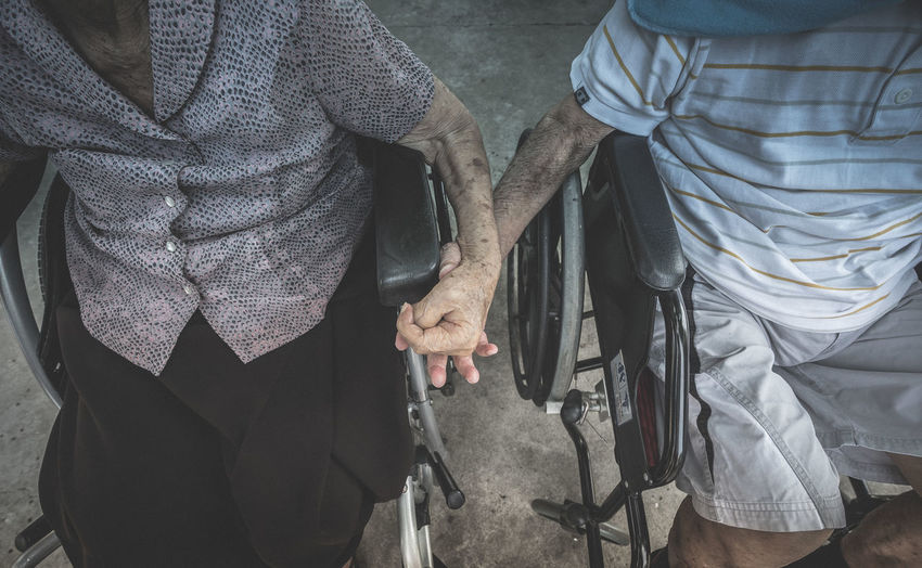 Midsection of couple sitting on wheelchairs holding hands