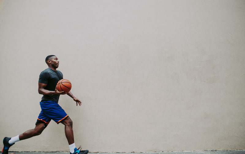 Young man playing basketball against wall