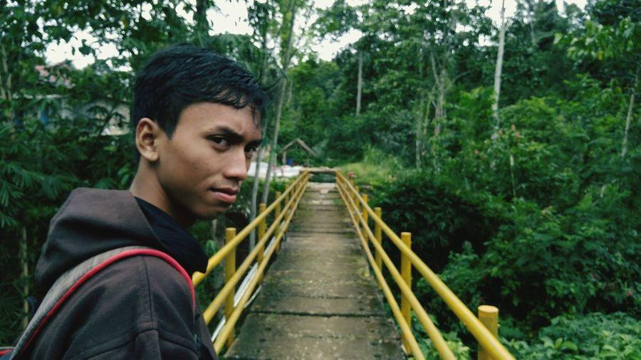 Portrait of teenage boy standing on footbridge amidst trees in forest