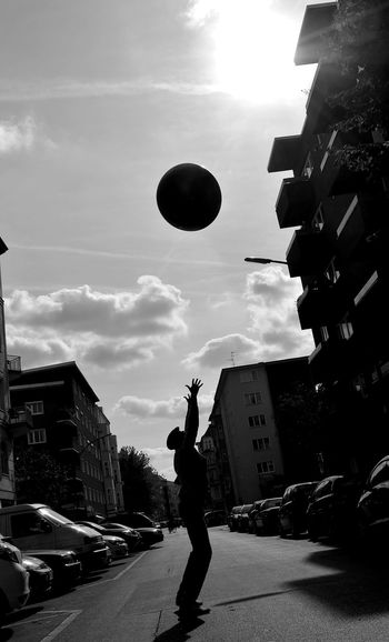 Side View Of Silhouette Man Catching Ball On Street During Sunny Day