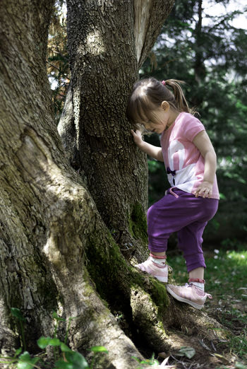 Full length of girl with tree trunk