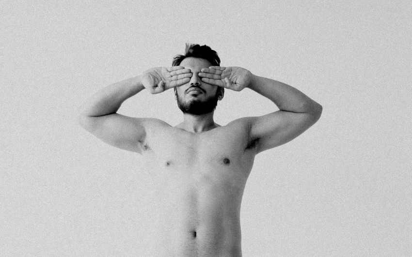 Shirtless Young Man Covering Eyes Against White Background
