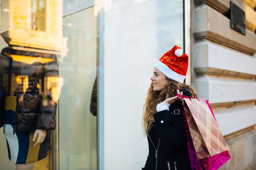 Young attractive woman with santa claus hat in front of shopping window looking to buy something Boutique Business Sale Shopping Standing Window Shopping Beautiful Woman Buying Consumerism Customer  Gift Hat Leisure Activity One Person Retail  Retail Display Santas Hat Shopaholic Shopping Bag Shopping Mall Store Store Window Street Window Young Women