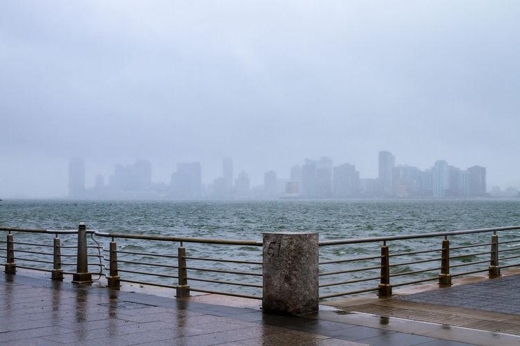 Skyline seen from promenade by sea in foggy weather
