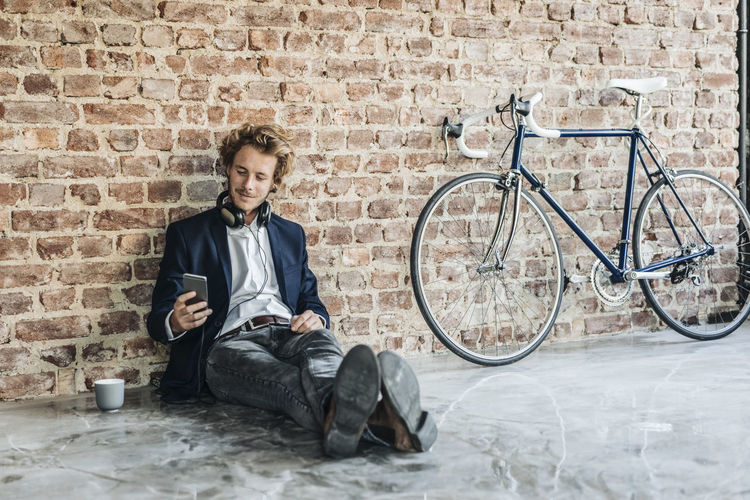 Young man with bicycle sitting against wall
