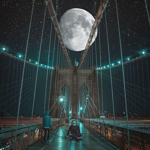 Rear view of people on footbridge at night