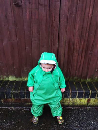 High Angle View Of Boy Wearing Green Raincoat Against Wooden Fence