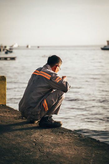 Full length of man crouching on pier by harbor