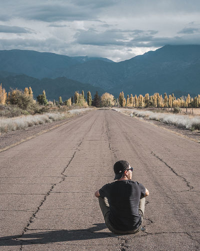 Rear view of man sitting on road against mountains