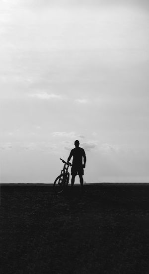 Silhouette man standing with bicycle on field against sky