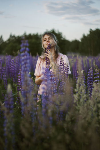 Young woman standing on flowering field