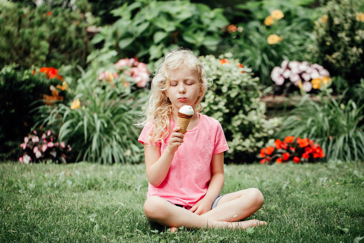 Cute funny girl sitting on grass in park eating licking ice cream from waffle cone.