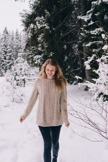 Young woman standing on snow covered land