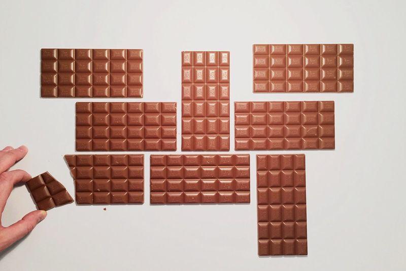 Hand arranging chocolate bars on white background