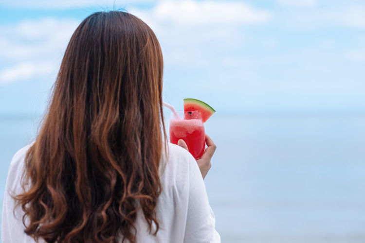 Rear view of woman holding watermelon at beach