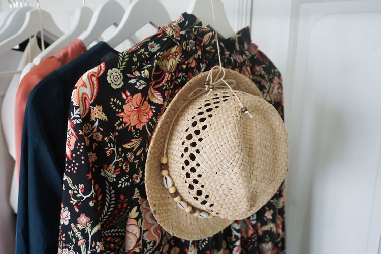 cloths and a hat hanging on a cloths rack Clothing Cloth Clothes Hanging Rack Fashion Fabric Textile Womenswear Straw Hat Hat Coathanger Textile Hanging Fashion High Angle View Close-up