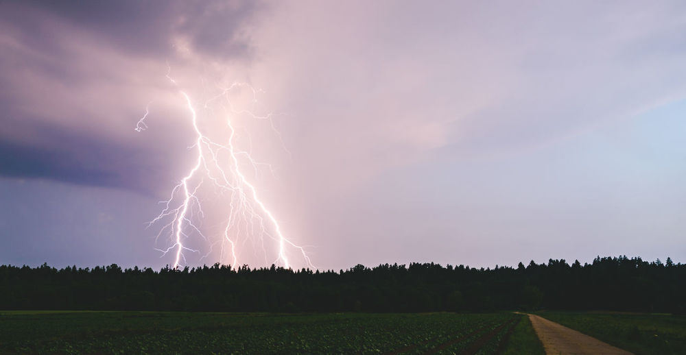 Scenic view of lightning over field against sky