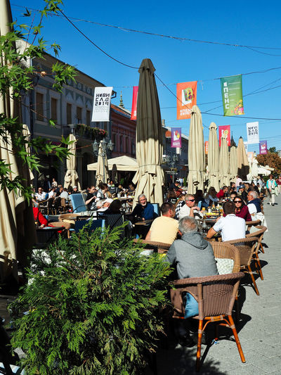 European Cities Novi Sad Serbia Eastern Europe Balkans Europe Outdoors Sunlight And Shadow Cityscape City Life Public Places Building Exterior Architecture Built Structure Day Building Street Photography City Outdoor Cafe Leisure Activity Group Of People Chair Seat Flag Table Text Plant