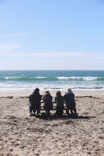 Rear View Of People Sitting On Bench At Moss Landing State Beach Against Sky