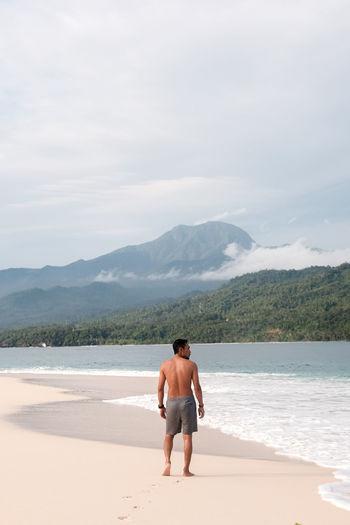 Rear view of shirtless man standing on banana island