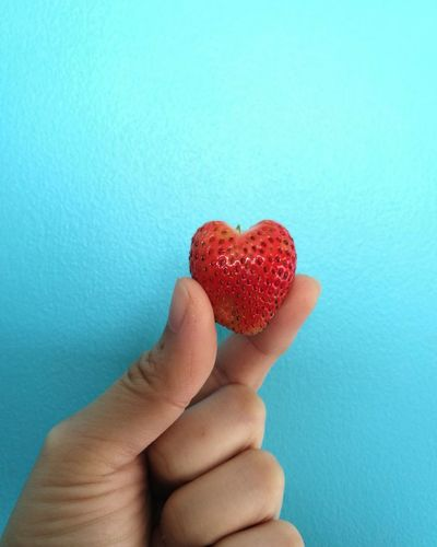Close-up of hand holding strawberry heart shape