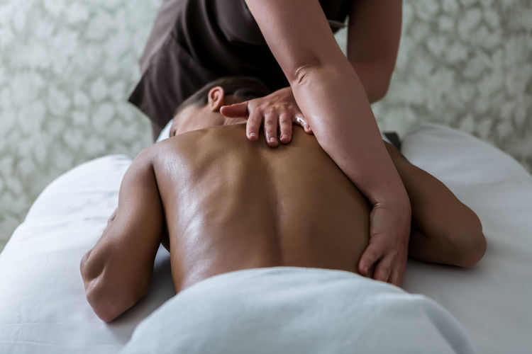 Midsection of masseur massaging woman lying on bed at spa