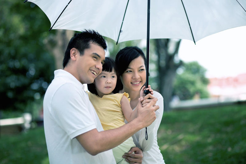 Happy family with white umbrella looking away at park