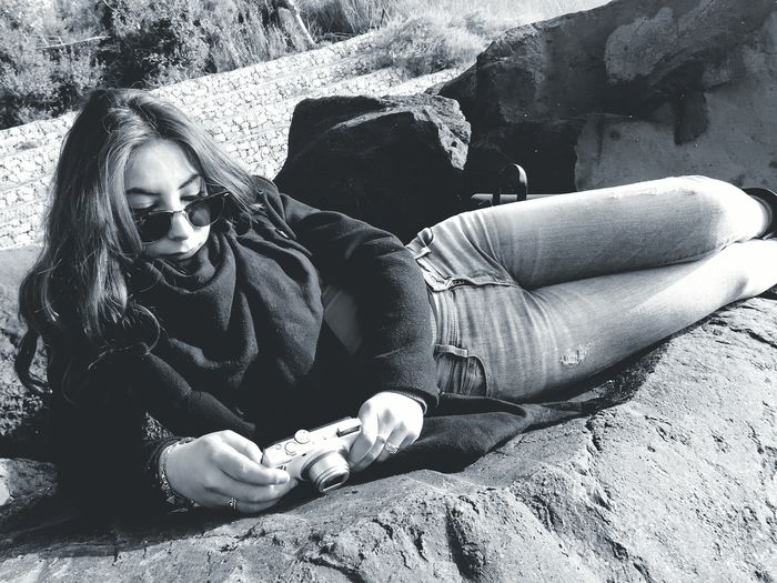 Woman using camera while reclining on rock