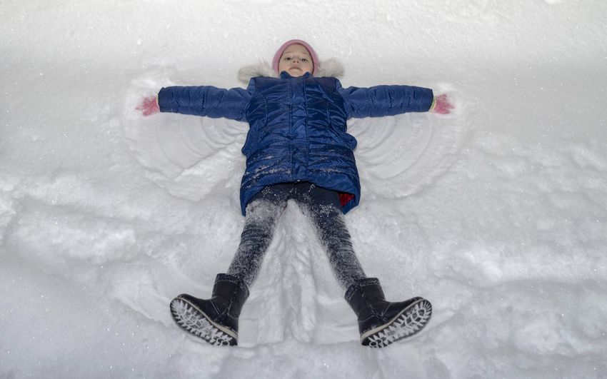 High angle portrait of girl making snow angel