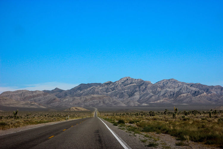 Beauty In Nature Blue Clear Sky Desert Landscape Mountain Mountain Range Nature Nevada No People Outdoors Physical Geography Road Scenics The Way Forward Tranquil Scene Transportation