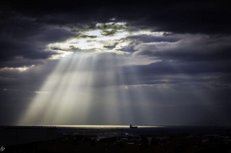 Sunlight streaming through storm clouds over sea