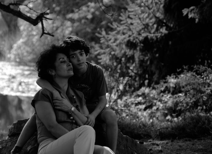Portrait Of Mother And Son Sitting In Forest