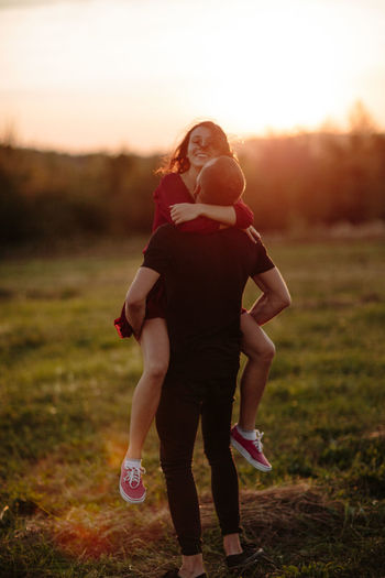 Rear View Of Man Picking Up Happy Girlfriend On Field During Sunset