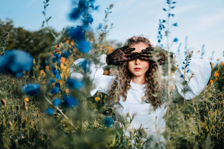 Beautiful young woman  with lace gloves standing in wild flowers in summer