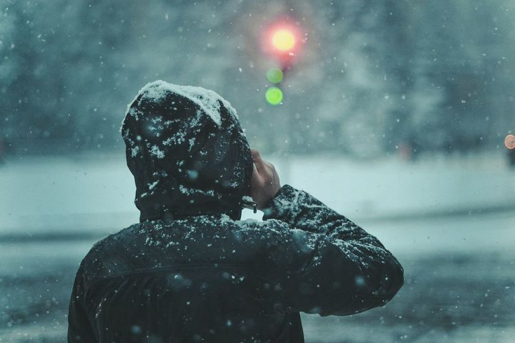 Rear view of person standing against illuminated stoplight during snowfall