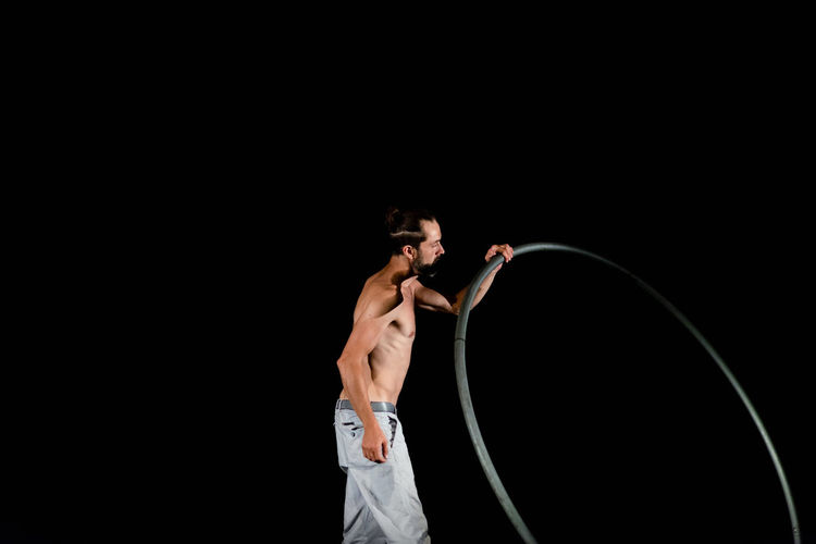 Circus Adult Arms Raised Black Background Copy Space Effort Exercising Healthy Lifestyle Holding Human Arm Indoors  Men Muscular Build One Person Shirtless Skill  Sport Standing Strength Studio Shot Three Quarter Length Young Adult Young Men