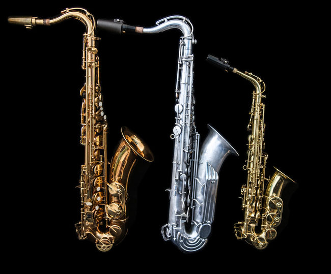 Three saxophones of different size. Sax Standing Arts Culture And Entertainment Black Background Brass Brass Instrument  Gold Color Gold Colored Indoors  Jazz Music Metal Music Musical Instrument No People Saxophone Shiny Silver Colored Size Studio Shot Three Objects Wind Instrument