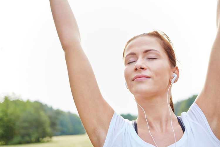 Close-Up Of Young Woman With Eyes Closed Exercising Against Sky