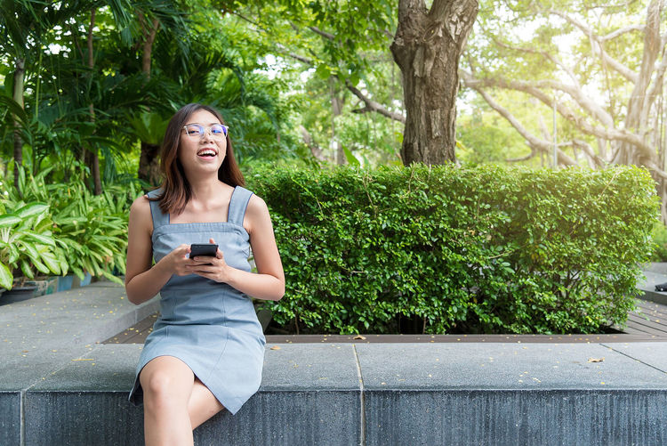 Smiling young woman using phone while sitting on tree