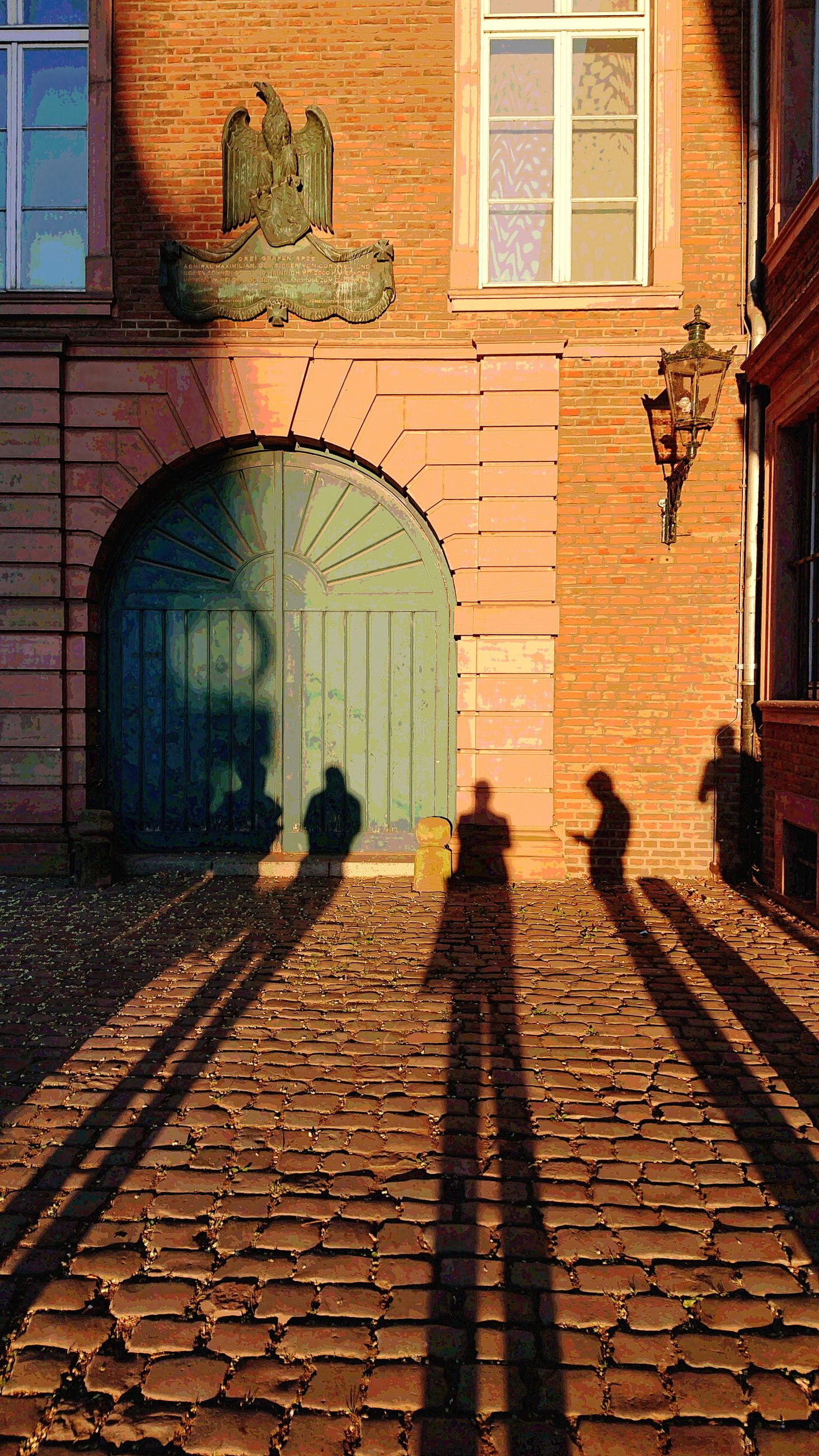 architecture, built structure, building exterior, shadow, real people, building, window, wall, people, men, cobblestone, sunlight, walking, day, group of people, street, adult, lifestyles, nature, outdoors, focus on shadow, brick