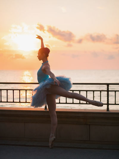 Woman ballet dancing by railing against sea