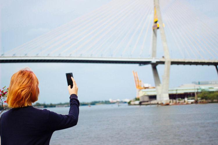 Low section of woman photographing on mobile phone against sky