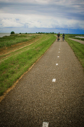 Rear View Of Friends Riding Bicycles On Road Against Cloudy Sky