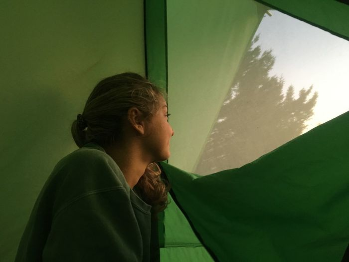 Young woman looking through tent