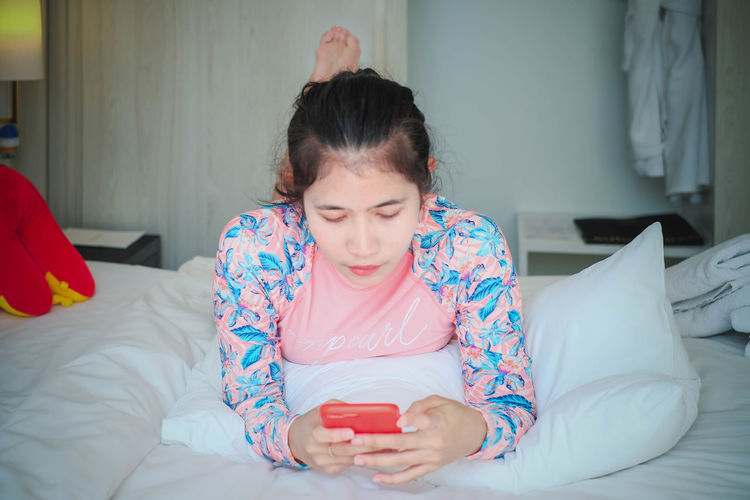 Girl looking away while relaxing on bed at home
