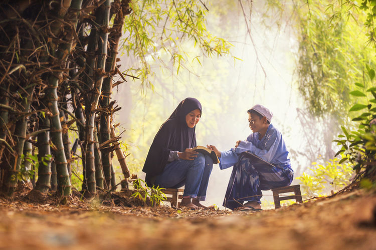 Asian muslim dress sitting reading quran books of islam and the brother in the bamboo forest.