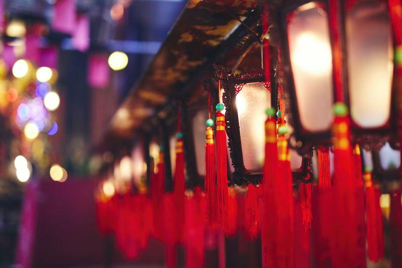 Close-up of illuminated lanterns hanging in row at night