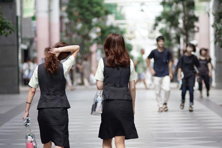 Rear view of women walking outdoors